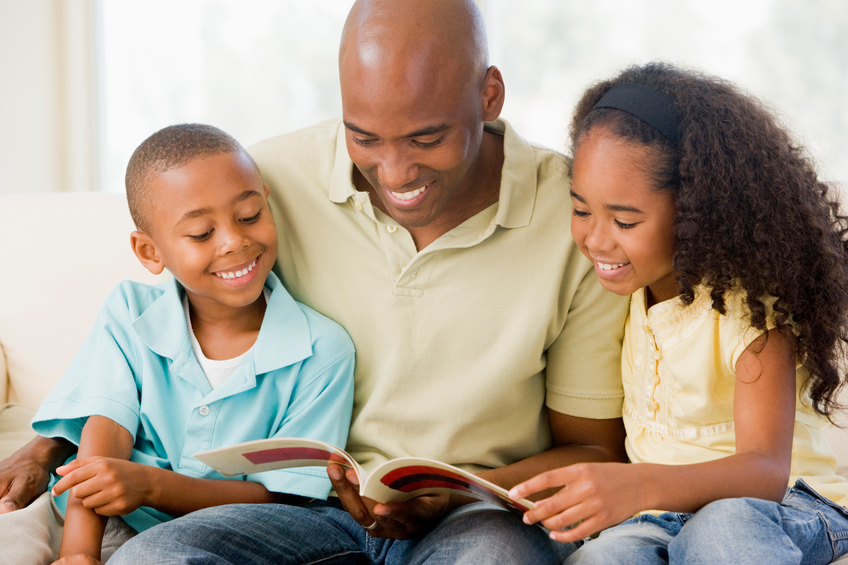 Man and two children sitting in living room reading book