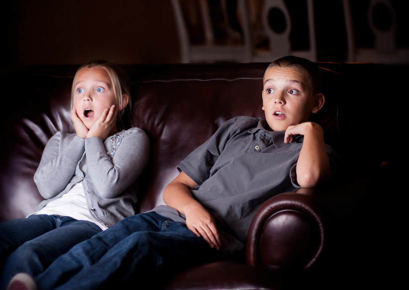 Two children on the couch acting shocked by the television